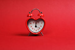 Time for love. Red heart shaped alarm clock on red background Stock Photos