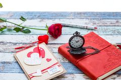 Time for love: red rose, heart, and journal with pocket watch Stock Image