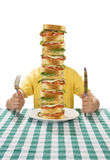 Time for Lunch. Giant sandwich on a white plate, with hands holding a a knife and fork on a table cloth royalty free stock images