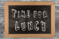 Time for lunch -  chalkboard with outlined text. On wood Royalty Free Stock Photo
