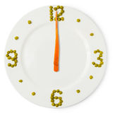 Time of lunch, сlock from plate, carrots and green peas Royalty Free Stock Photography