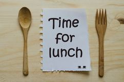 Time for lunch written on note between spoon and fork Stock Photos