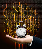 Time machine concept. Clock on hand with circuit board graphic background Royalty Free Stock Image