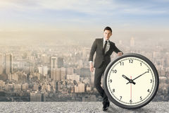 Time manage. Asian businessman standing with a clock, concept of time manage or plan royalty free stock images