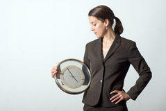 Time Management. A business woman holding a clock with her hand on her hip Royalty Free Stock Image