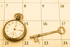 Time Management. A pocket watch and a key on a calendar background, time management Royalty Free Stock Photos