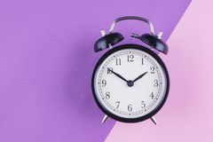 Time management concept, alarm clock on purple background. Copy space for text stock photos