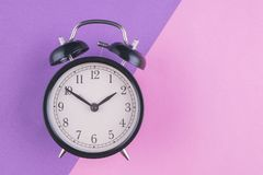 Time management concept, alarm clock on purple background. Copy space for text stock photography