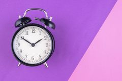 Time management concept, alarm clock on purple background. Copy space for text royalty free stock images