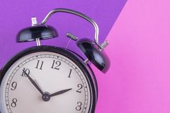 Time management concept, alarm clock on purple background. Copy space for text stock image