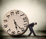 Time management concept. Businessman buckled under time pressure with a clock-reversed face.  Time management concept Stock Images