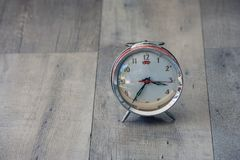 Time Management Concept : Close up red vintage alarm clock be distorted and damaged setting on wooden floor. Time Management Concept : Close up red vintage Stock Images