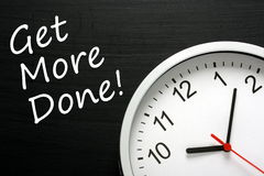 Time Management Concept. The phrase Get More Done written on a blackboard next to a modern office wall clock Royalty Free Stock Image