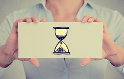 Time management concept. Woman hands card with sand clock sign Royalty Free Stock Photography