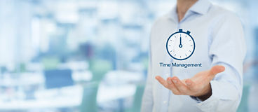 Time management. And deadline concept. Businessman with clock watch expecting deadline. Wide banner composition with out of focus office in background Stock Photos