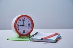 Time management, deadline and schedule concept: alarm clock and notebook on blue background.  royalty free stock photos