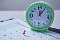 Time management, deadline and schedule concept: alarm clock and pushpin on schedule plan. Time management, deadline and schedule concept: alarm clock and royalty free stock photos