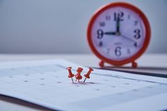 Time management, deadline and schedule concept: alarm clock and pushpin on schedule plan. Time management, deadline and schedule concept: alarm clock and royalty free stock photo