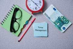 Time management deadline and schedule concept: clock, notebook and stack of bills on grey background. Flat lay.  stock photos