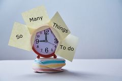Time management deadline and schedule concept: clock with stickers on the stack of stickers.  stock photos