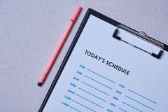 Time management deadline and schedule concept: schedule sheet and pen on grey background.  stock image