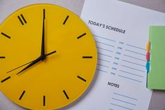 Time management deadline and schedule concept: yellow clock on the background of the schedule.  royalty free stock photo