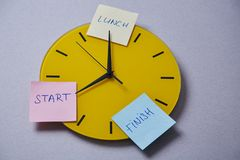 Time management deadline and schedule concept: yellow clock covered with stickers.  royalty free stock image