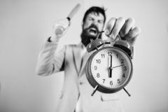 Time management and discipline. Discipline and sanctions. Boss aggressive face hold alarm clock. Destroy or turn off. Man suit hold clock and baseball bat in royalty free stock image