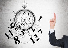 Time management finger up. Time management concept with broken clock and businessman putting one finger up on concrete background Royalty Free Stock Images
