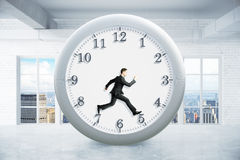 Time management in interior. Time management concept with running businessman inside clock on empty interior background. 3D Rendering Royalty Free Stock Images