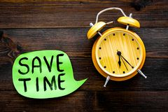 Time-management. Save time hand letterng in cloud near alarm clock on dark woodem background top view copy space. Time-management. Save time hand letterng in royalty free stock image