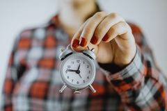 Time management. Small alarm clock in female hands Royalty Free Stock Photography