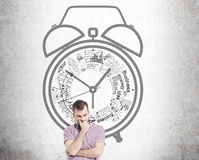 Time management with thoughtful man. Time management concept with thoughtful  young man against concrete wall with alarm clock sketch Royalty Free Stock Photos