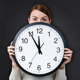 Time management for woman. Concept. Woman with an office clock against chalkboard background Royalty Free Stock Images