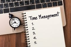 Time management with list on notebook. Time management concept with list on notebook and clock on computer from top view stock image