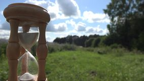 Time measure with wooden sandglass on fields and sky background. 4K stock video