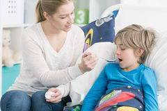 Time for the medication. Shot of a young mother giving his son a medication Stock Photography