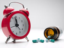 Time for the medicine. Clock  and pills over white background,closeup, for health care,medicine,addiction themes Stock Image