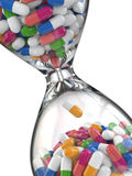 Time of medicine. Pills in hourglass Stock Images