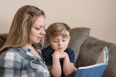 Time With Mom. A young boy listens attentively as his mother reads to him Royalty Free Stock Photos