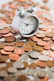 Time is money... Coins & alarm clock - shallow dof Stock Images