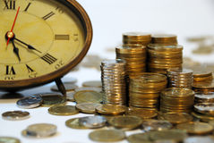 Time is money... Old hours and different coins - symbol Royalty Free Stock Photos