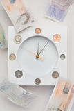 Falling pound. Clock displaying coins with banknotes flying around, clock hands in motion Stock Photos