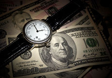 Time is money. Watches and 100 dollar bills Stock Images
