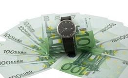 Time is money. Watch and one hundred euro banknotes isolated on a white Stock Photo