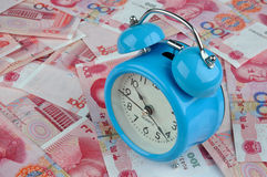 Time and money. A blue clock with money note, means time is cost or value, and always relate to fortune and rich Royalty Free Stock Images