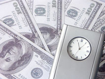 Time is money. One hundred dollar bills and clock stock images