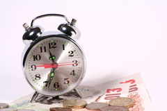Time is money. A alarm clock and some mony in pounds Stock Photo
