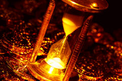 Time is Money. Hourglass and Gold Coins Stock Image