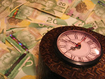 Time is Money 2. Time is money concept / metaphor with antique clock and cash bills in background royalty free stock photo